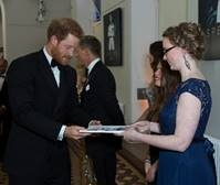 Young ShelterBox intern Grace Howarth presents Prince Harry with a souvenir brochure for the Royal Film Performance at the Royal Albert Hall in October 2015