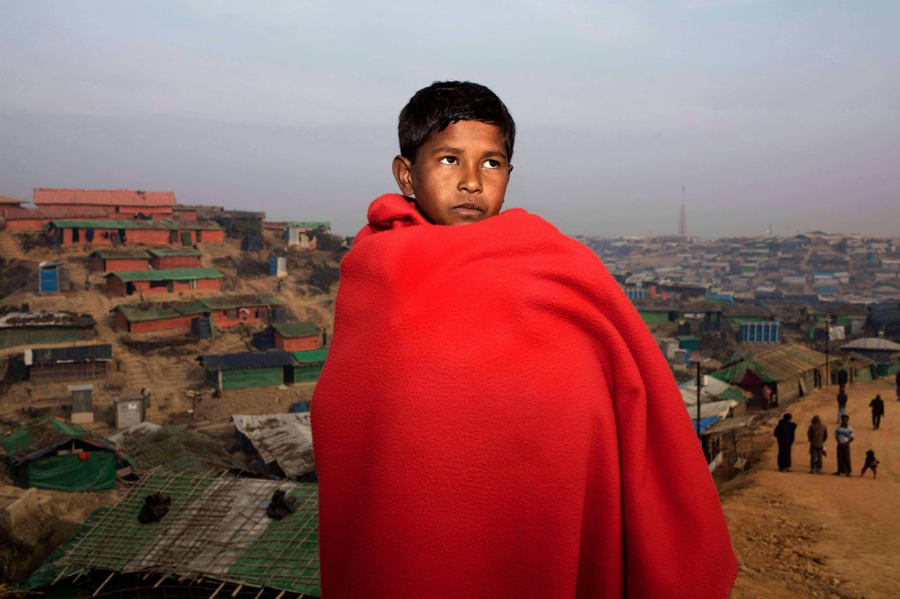 A young boy stands in front of a city with a red blanket wrapped around him