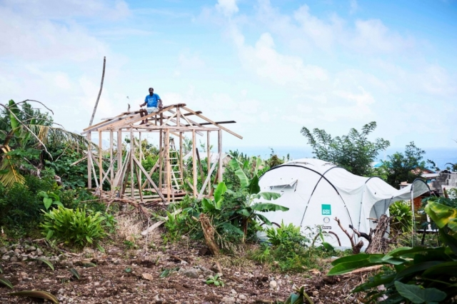 A man sits on the roof of a structure he is beginning to build with his ShelterBox tent nearby