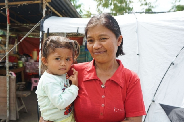 A woman stands with a young child in her arms in front of a ShelterBox tent