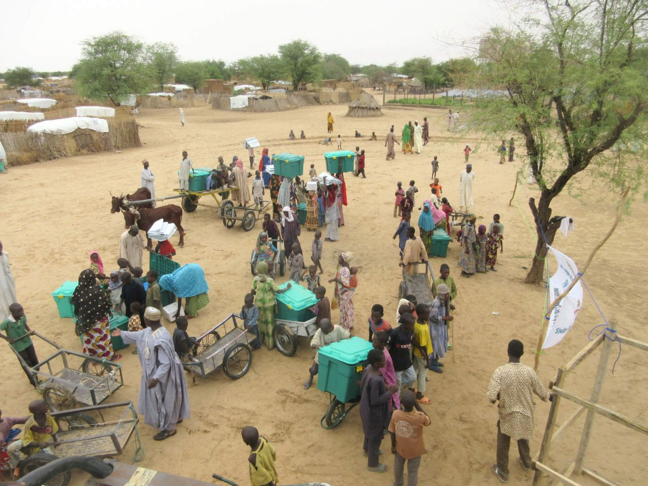 A group of people stand in the middle of a large clearing, using bikes and wagons to carry ShelterBoxes