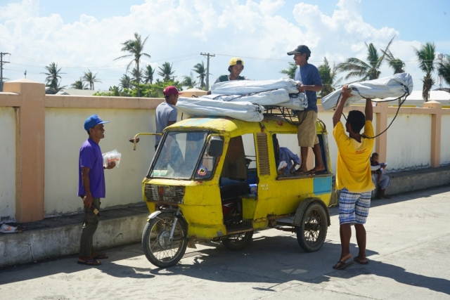 A group of men stack ShelterKits on top of their three-wheel vehicle.