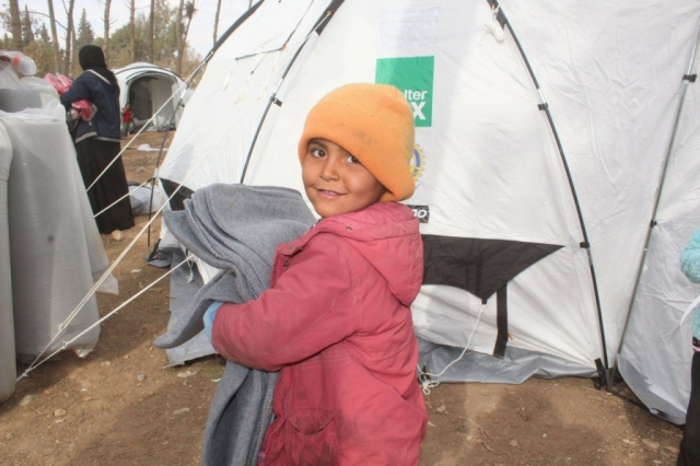 A boy stands holding blankets in front of a ShelterBox tent.