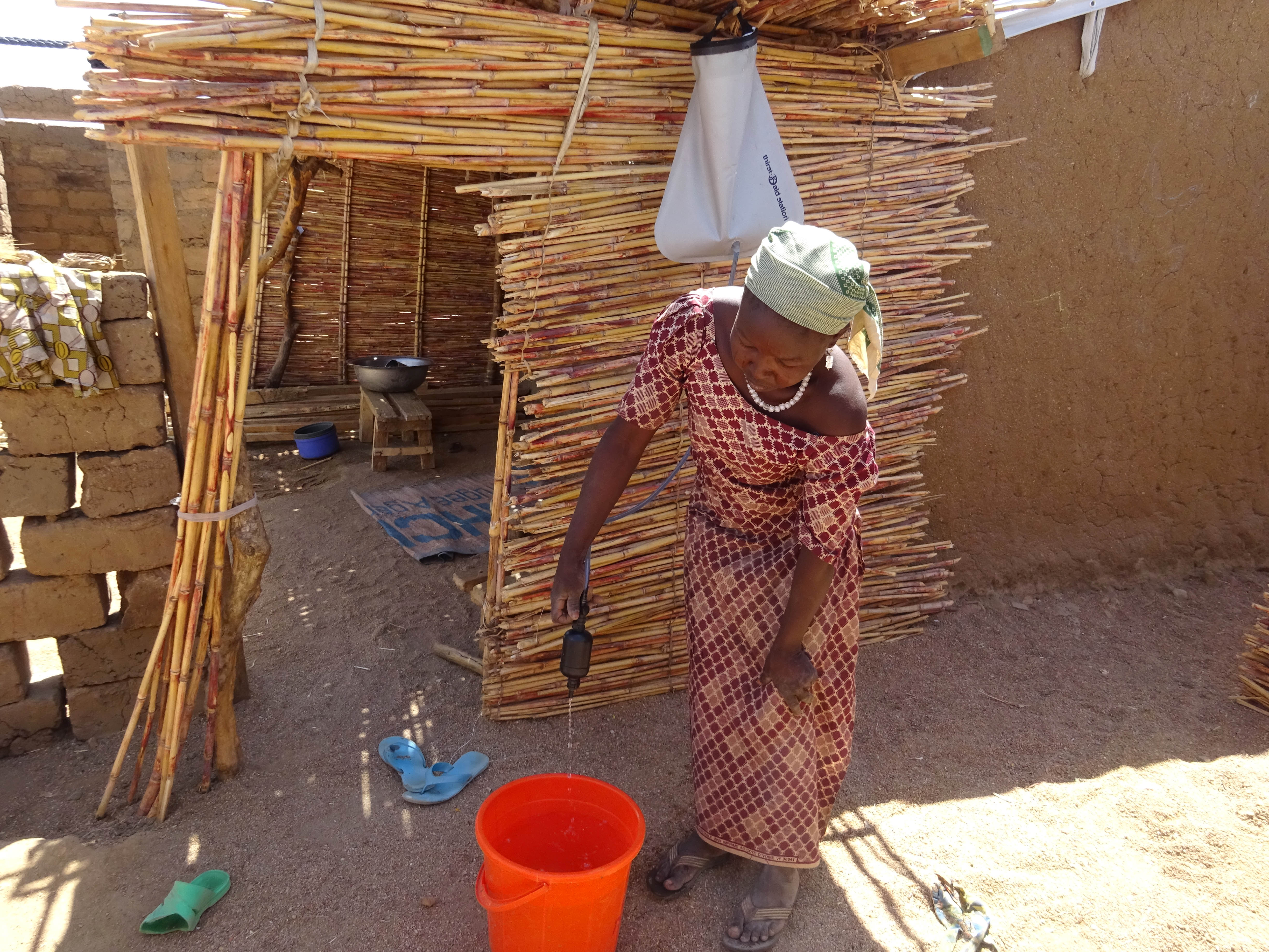 A woman filters water into a bucket