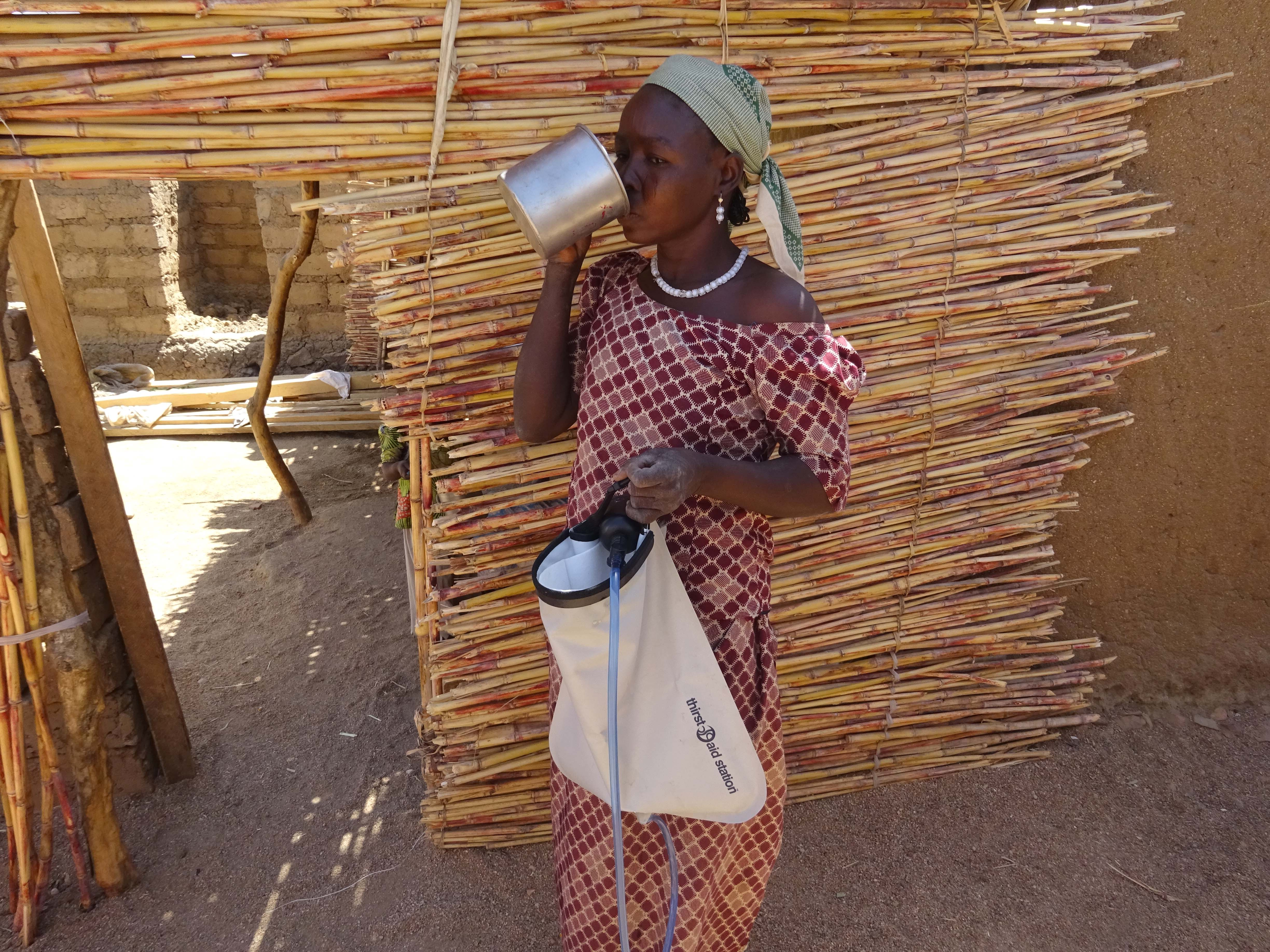 A woman drinks water out of a cup and holds a water filter