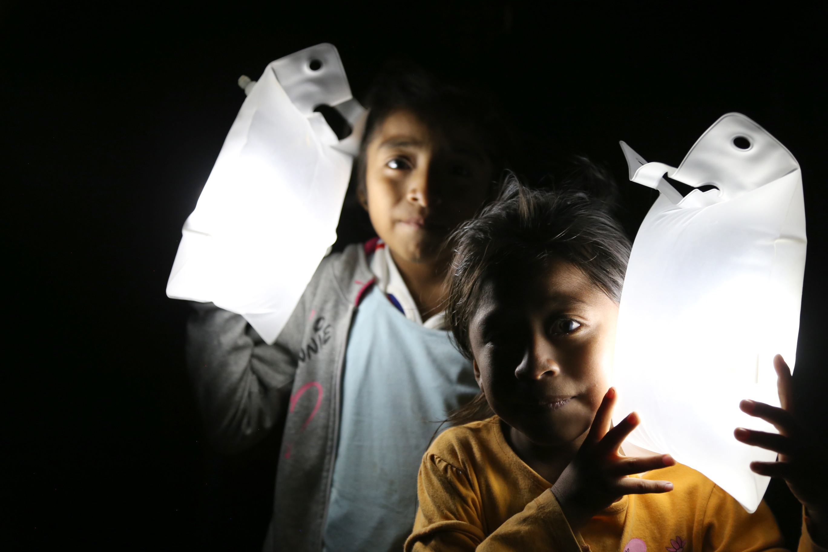 Children in Peru carry their solar lights in the dark