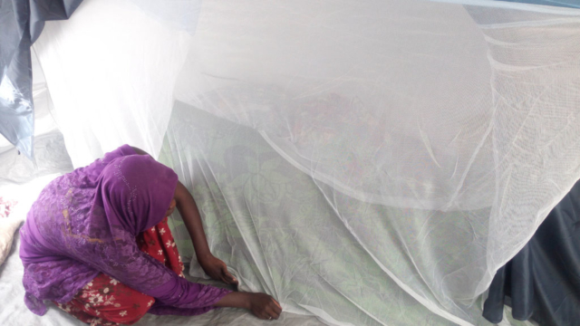 A woman crouches on the floor pulling the edge of a mosquito net to the ground