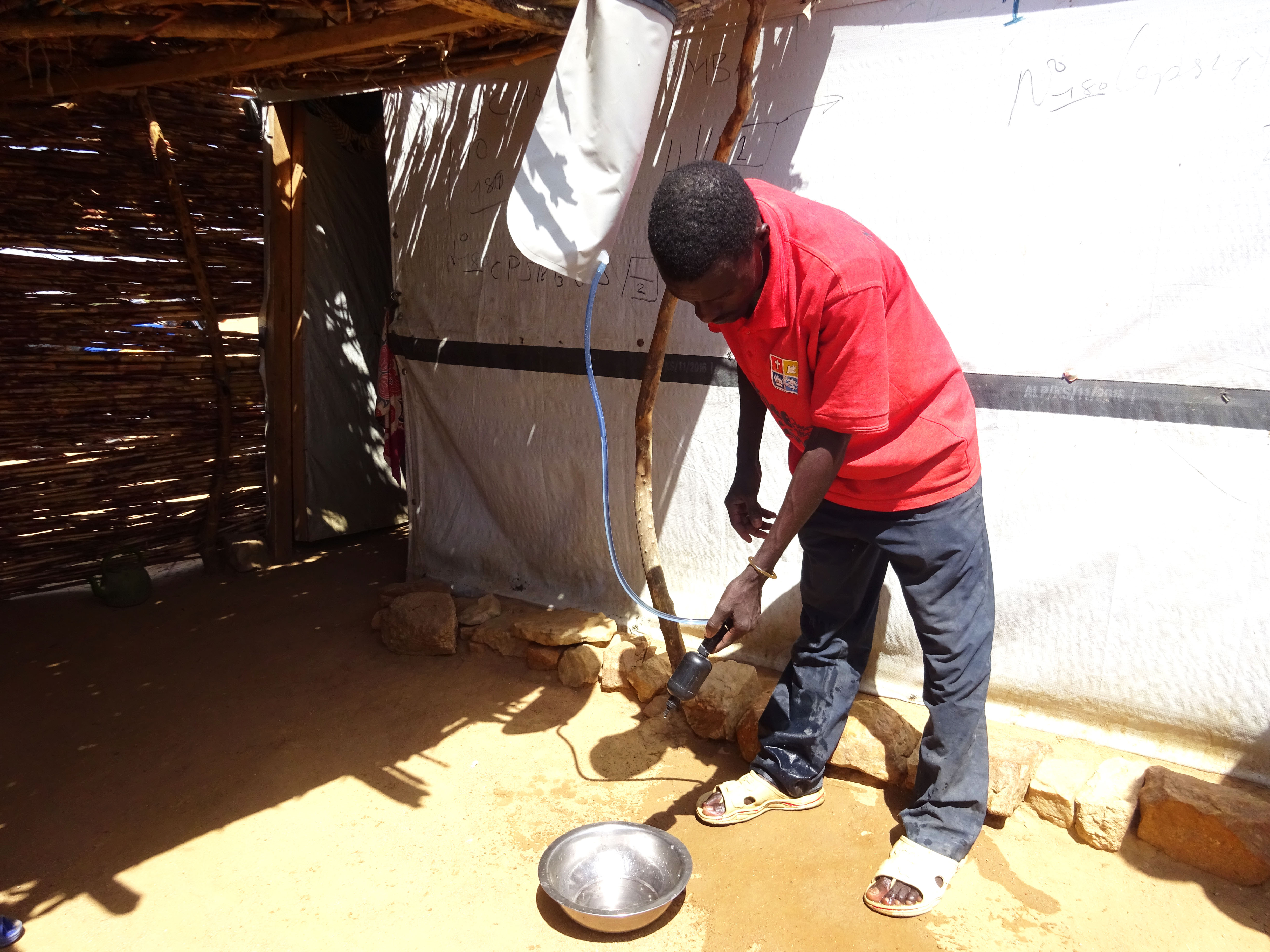 A man holds the hose from a water filter bag as water drips into a bowl on the ground