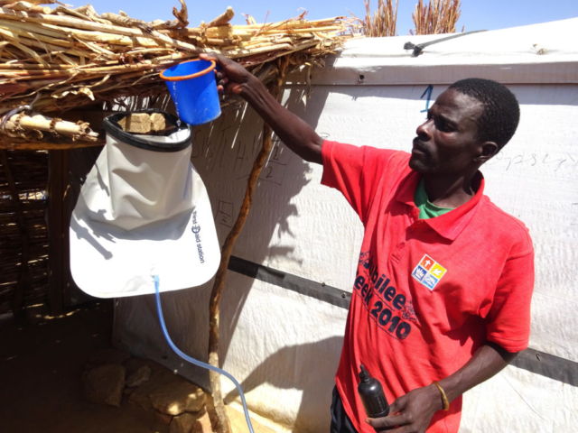 A man pours water from a pail into a water filter bag