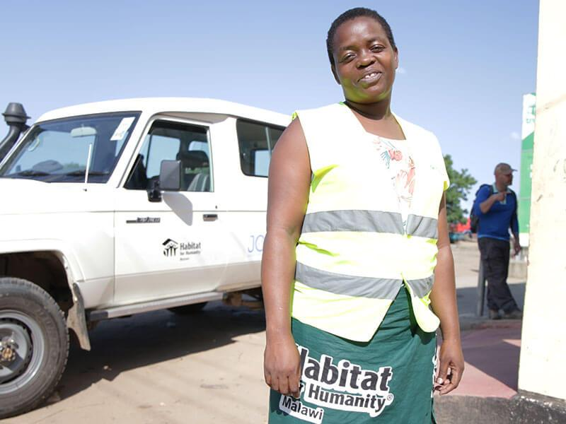 A woman stands next to a truck wearing a Habitat for Humanity vest.