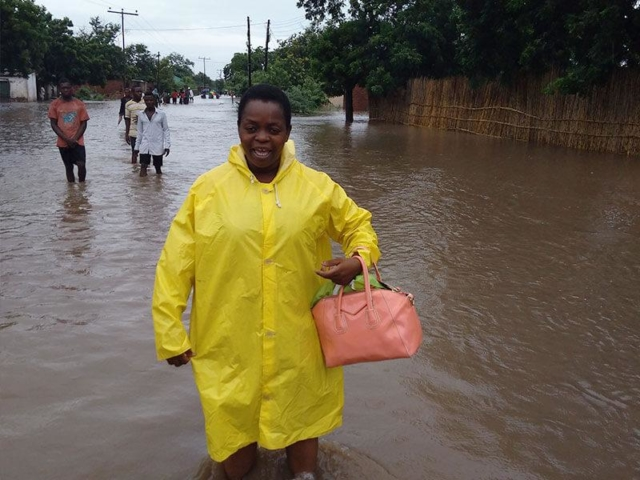 A woman wearing a yellow raincoat stands in water that is up to her knees after flooding in Malawi.