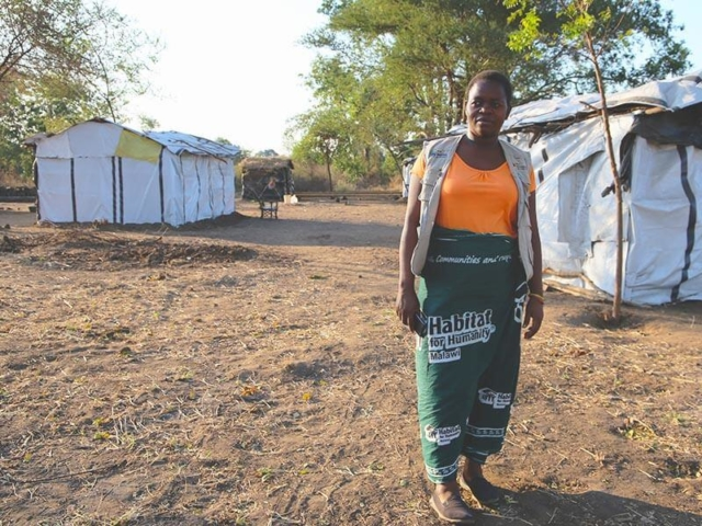 A woman wearing a Habitat for Humanity skirt stands in a field with make-shift shelters around her.