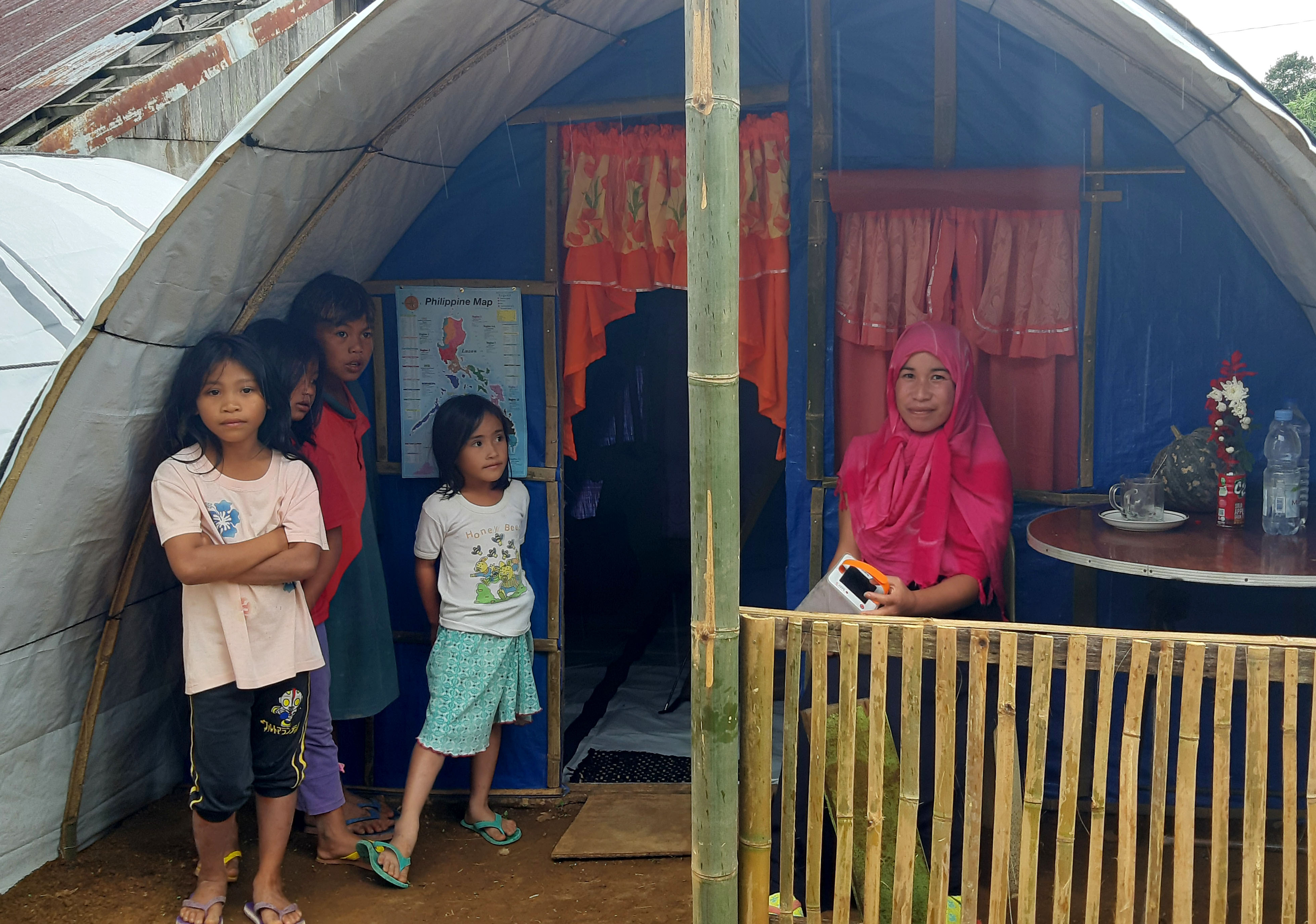A woman sitting in front of her shelter with four children