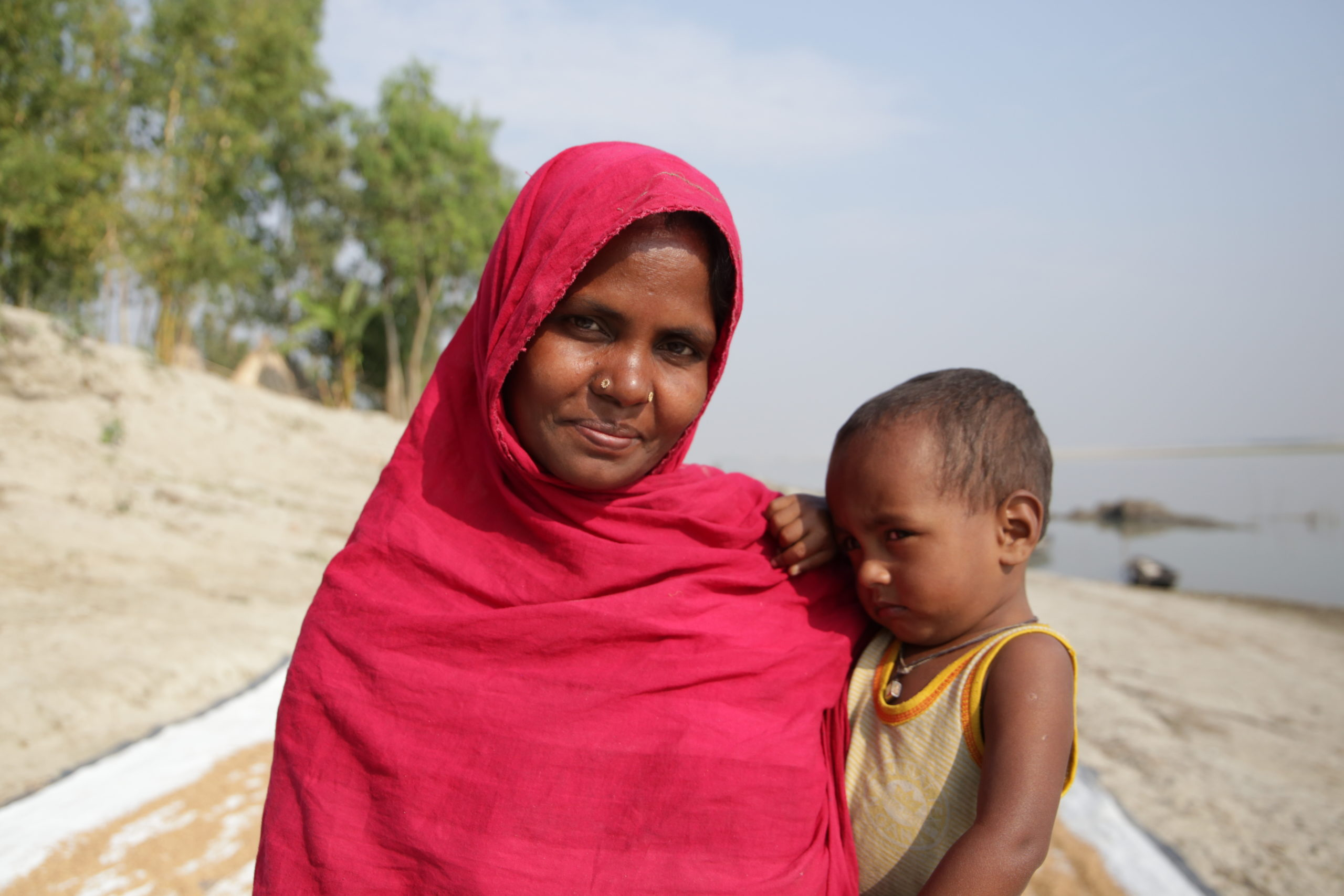 A woman stands on a beach holding a young child