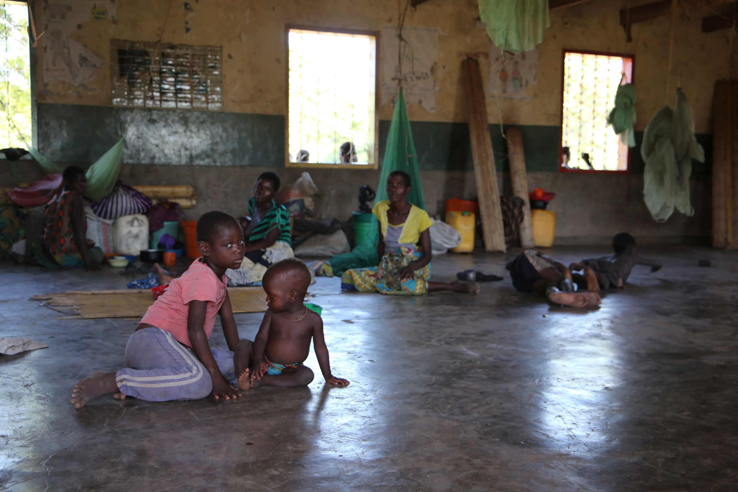 Foreground: two children sit on the concrete ground inside a school being used as an emergency shelter. Adults and other children can be seen in the background