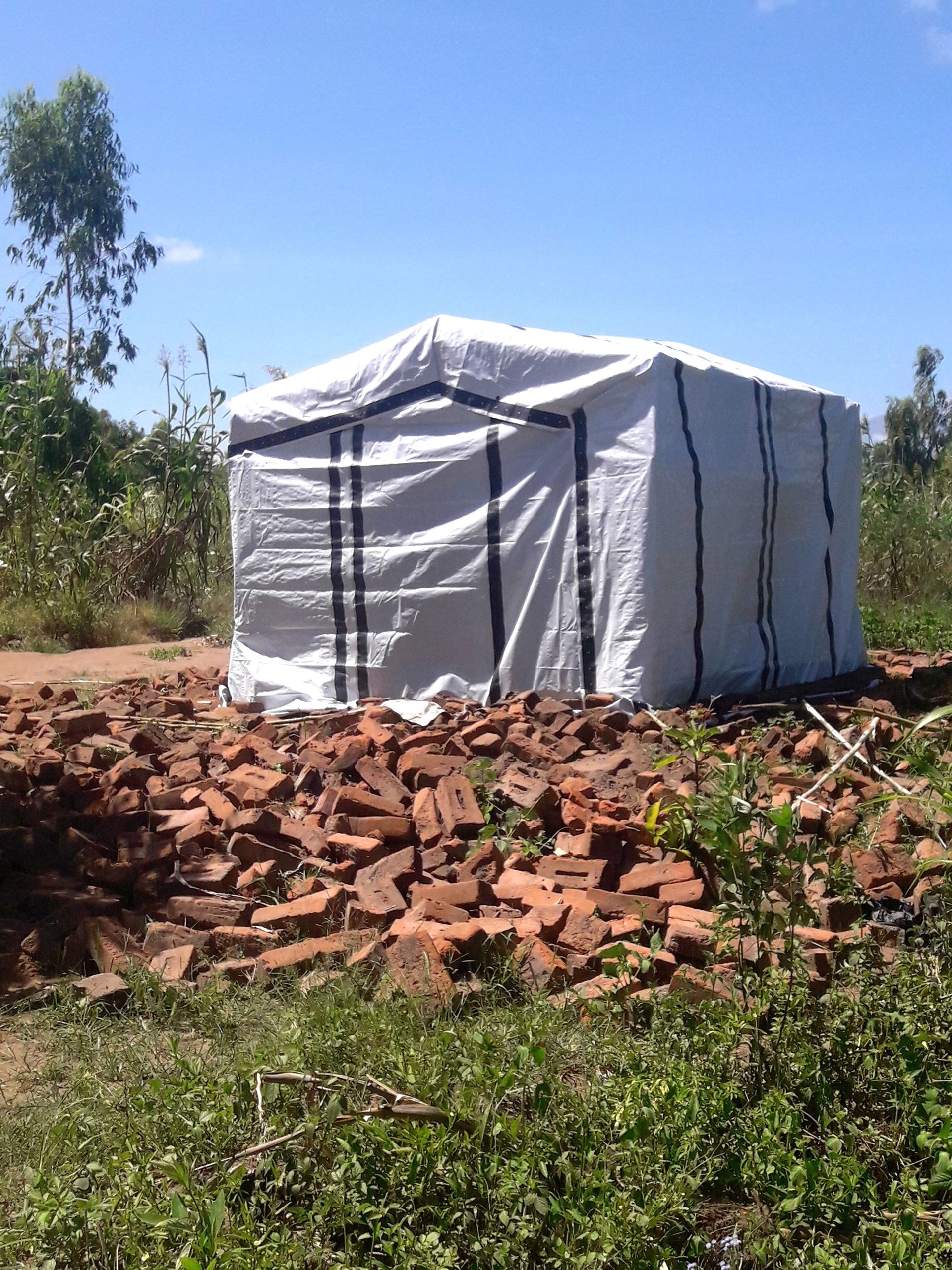a shelter structure made from ShelterKit materials stands in front of a pile of bricks