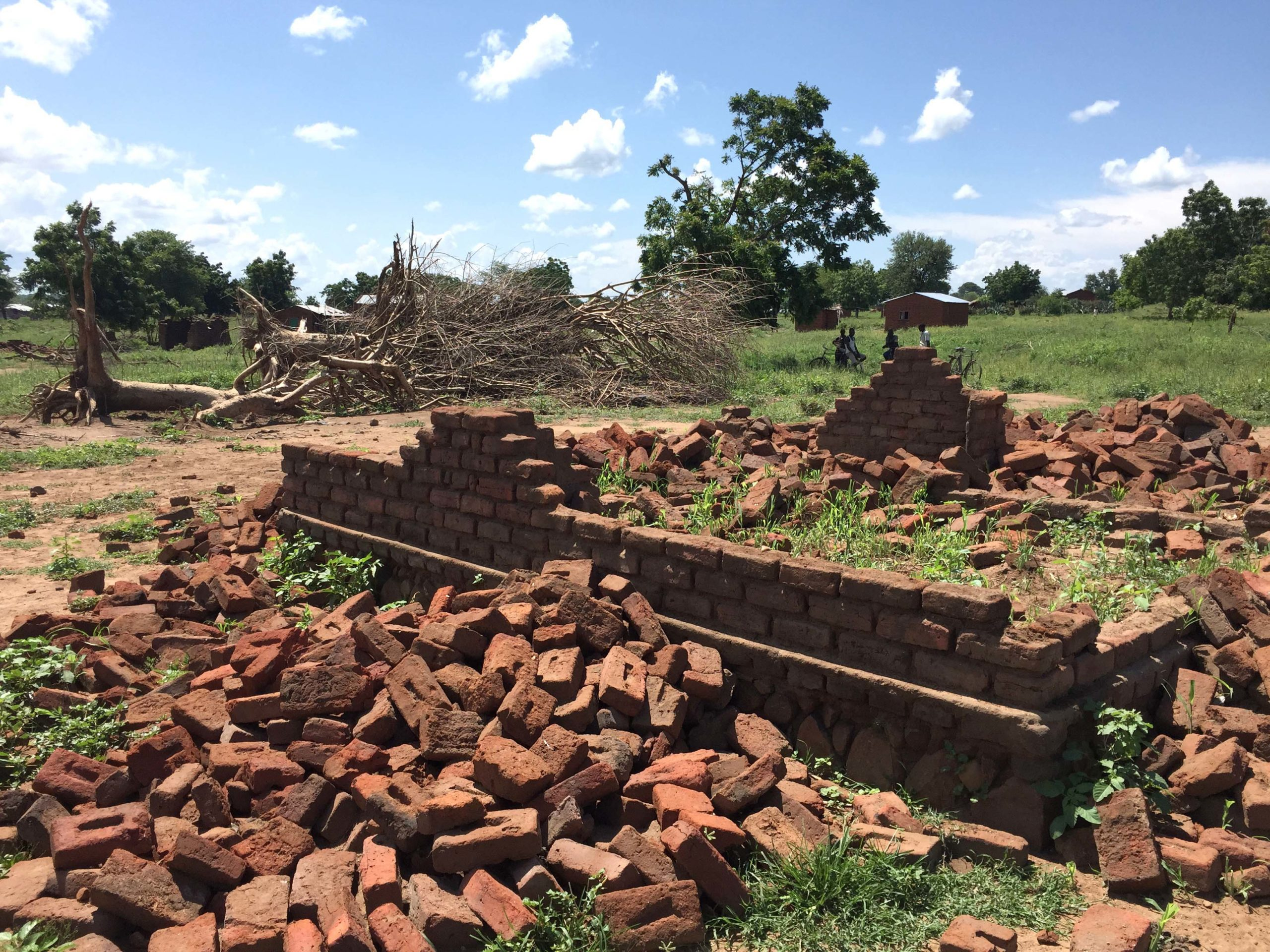 A pile of bricks surrounds the frame of a destroyed house in Malawi