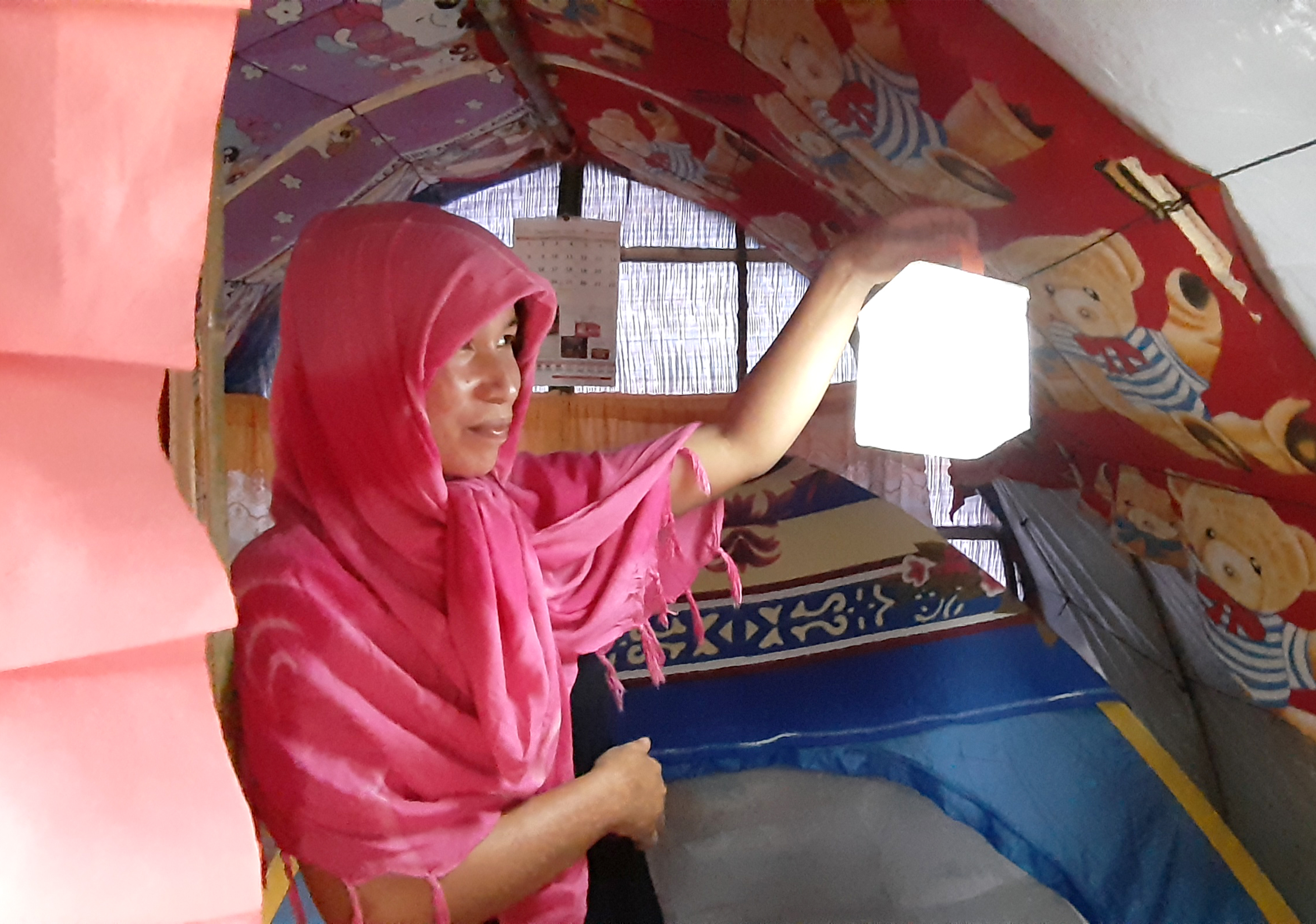 A woman stands in her shelter holding up a solar light that is lit
