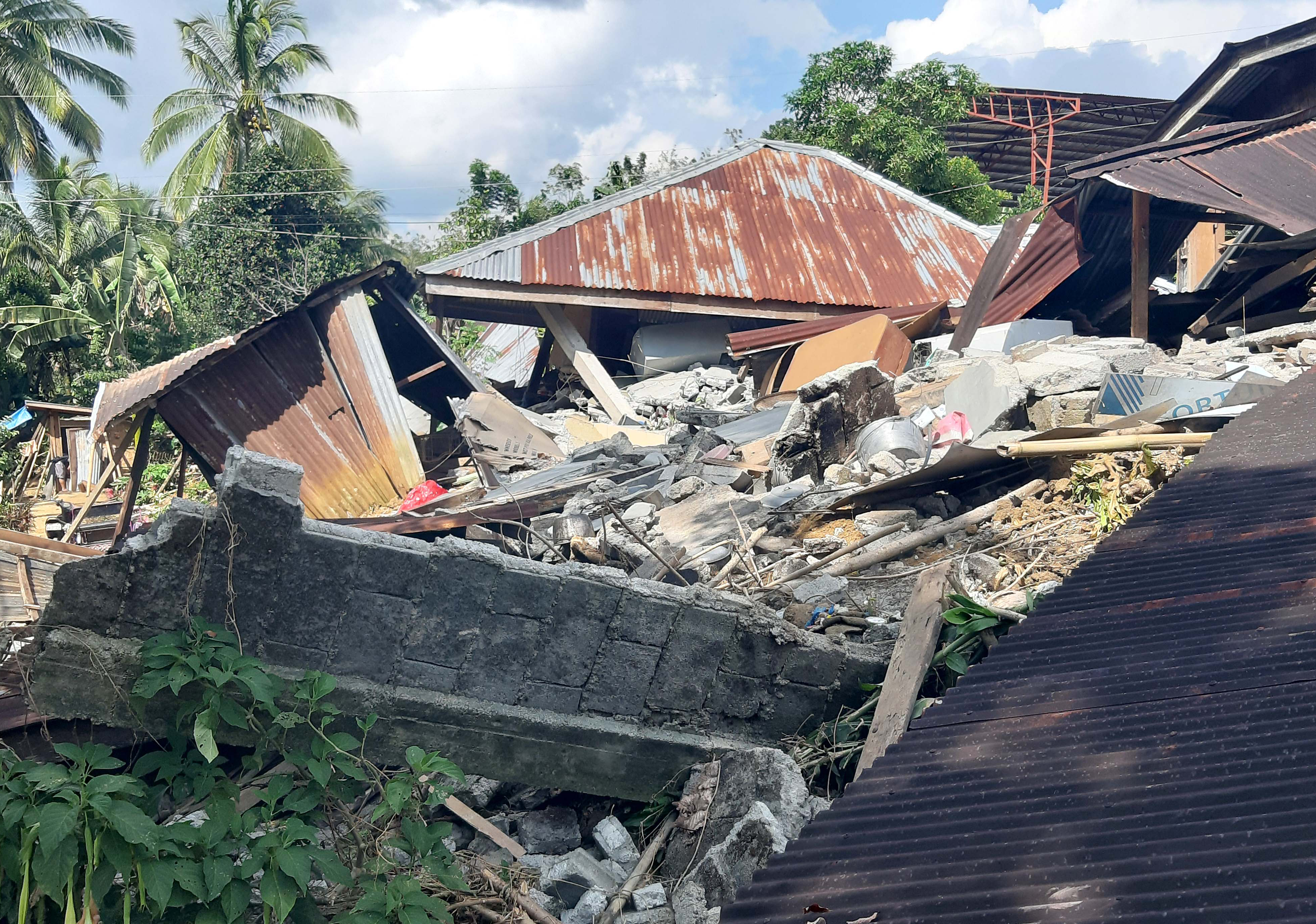 A destroyed house with rubble around it