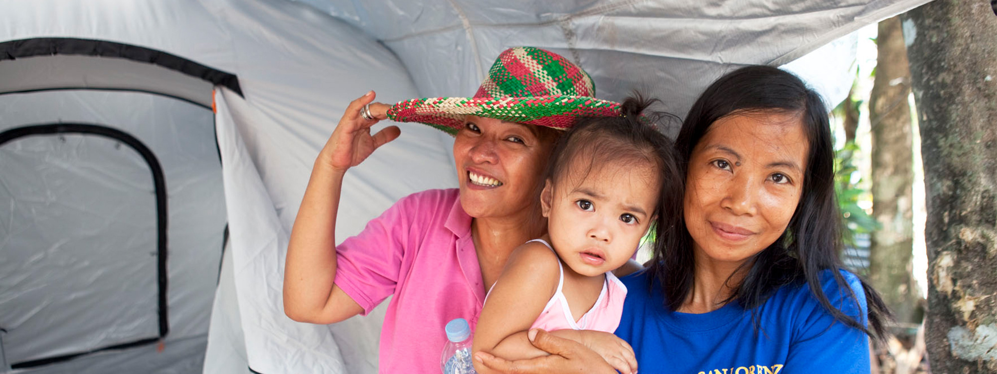 A woman holding a child stands next to another woman in front of a tent. The women are both smiling.